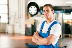 De werktuigkundige van de auto in workshop stock foto