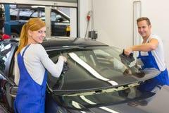 De werktuigkundigen of de glazenmakers installeren windscherm of voorruit op auto Royalty-vrije Stock Foto