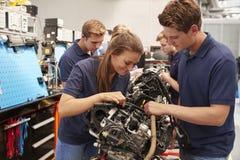 De werktuigkundigen die van de leerlingsauto aan een motor werken stock afbeelding