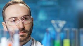 De wetenschap van de close-up mannelijke microbiologie arts die met reactief bij futuristische blauwe lichtenachtergrond werken stock videobeelden