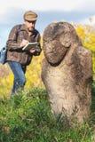 De wetenschappelijke historicus beschrijft steenbeeldhouwwerk op hoop royalty-vrije stock foto