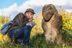 De wetenschappelijke historicus beschrijft steenbeeldhouwwerk op hoop stock fotografie