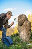 De wetenschappelijke historicus onderzoekt door scu van de vergrootglassteen stock foto's