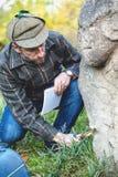 De wetenschappelijke historicus onderzoekt door scu van de vergrootglassteen stock afbeeldingen