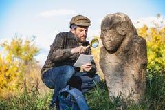 De wetenschappelijke historicus onderzoekt door scu van de vergrootglassteen royalty-vrije stock afbeeldingen