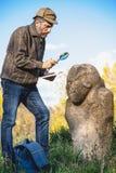 De wetenschappelijke historicus onderzoekt door scu van de vergrootglassteen stock afbeelding