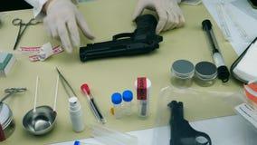 De wetenschappelijke Politie opent bewijsmateriaalzak met kanon voor analyse stock video