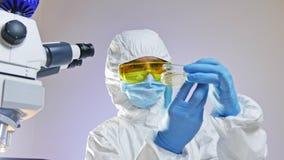 De wetenschapper bekijkt een petrischaal met bacteriën door licht stock videobeelden