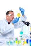De wetenschapper die van het laboratorium bij laboratorium met reageerbuizen werkt stock afbeeldingen