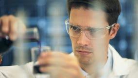 De wetenschapper die van het laboratorium bij laboratorium met reageerbuizen werkt stock videobeelden