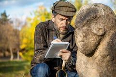 De wetenschapper en de historicus, beschrijven het beeldhouwwerk van de zittingssteen op mo stock fotografie