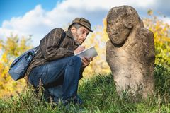 De wetenschapper en de historicus beschrijven het beeldhouwwerk van de zittingssteen op mou stock foto's