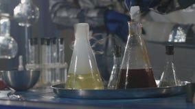 De wetenschapper en zijn medewerker leiden chemische experimenten in een ondergronds laboratorium in Langzame motie stock video