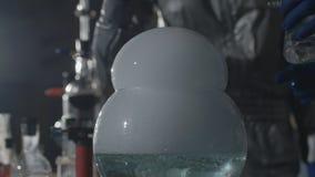De wetenschapper en zijn medewerker leiden chemische experimenten in een ondergronds laboratorium in Langzame motie stock videobeelden