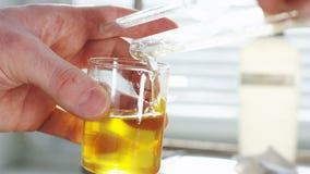 De wetenschapper giet duidelijke gele vloeistof in laboratoriumglas stock videobeelden