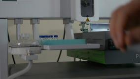 De wetenschapper houdt een chemische steekproeffles De arts dient medische handschoen met klinische chemiesteekproeven zettend in stock footage