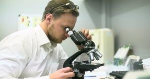 De wetenschapper kijkt door Microscoop en het Schrijven Gegevens over Tablet stock video