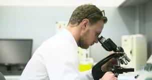 De wetenschapper kijkt door Microscoop en het Schrijven Gegevens over Tablet stock footage