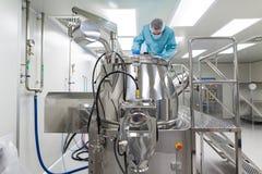 De wetenschapper kijkt in staaltank in laboratorium Stock Afbeeldingen
