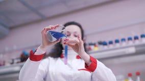 De wetenschapper mengt vloeistoffen in reageerbuizen stock videobeelden