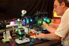 De wetenschapper met glas toont laser aan Royalty-vrije Stock Foto