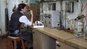 De wetenschapper overweegt plan van chemisch experiment in laboratorium stock videobeelden