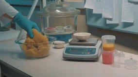 De wetenschapper in rubberhandschoen neemt kinetisch zand en zette het op elektronische gewichten stock video