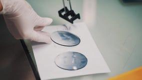 De wetenschapper in rubberhandschoenen zet natte glaslenzen op document blad in laboratorium stock footage