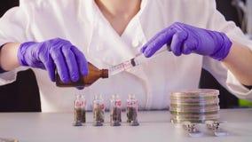 De wetenschapper ` s overhandigt gietend oplosmiddel in de flessen stock videobeelden