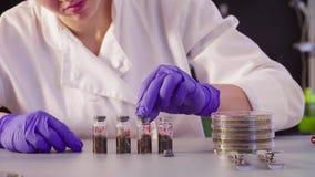 De wetenschapper ` s overhandigt handen dichte flessen met steekproeven stock footage