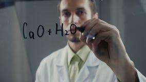 De wetenschapper schreef chemische formule op een bord stock videobeelden