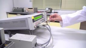 De wetenschapper is usin multifunctionele wetenschapsmeter aan metingsvoorwerp in het laboratorium van het innovatieonderzoek stock video