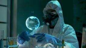 De wetenschapper van biotechniektechnologie of chemie in beschermende kleren bekijkt blauw gloedhologram van Aarde stock video