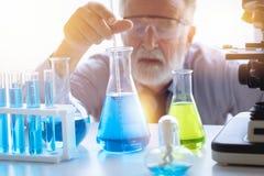 De wetenschapper van de chemieprofessor in wetenschaps chemisch laboratorium stock foto