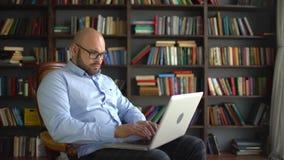 De wetenschapper werkt thuis laptop aan de achtergrond van de bibliotheek Nadenkende mannelijke wetenschapper die nieuw artikel t stock footage