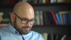 De wetenschapper werkt thuis laptop aan de achtergrond van de bibliotheek Nadenkende mannelijke wetenschapper die nieuw artikel t stock video