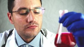 De wetenschapper ziet spruit in een reageerbuis Van hem dient handschoenen in stock video