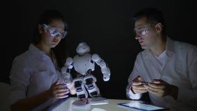 De wetenschappersmensen controleren functionaliteit moderne robot met kunstmatige intelligentie in laboratorium stock video