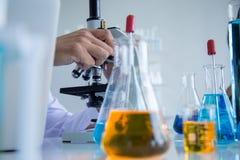 De wetenschapperwetenschapper kijkt door microscoop, in laboratoriumruimte royalty-vrije stock afbeeldingen