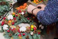 De wevende workshop van de Kerstmiskroon Vrouwenhanden die die vakantiekroon verfraaien van nette takken, kegels en diverse organ royalty-vrije stock foto