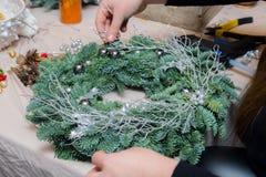 De wevende workshop van de Kerstmiskroon Vrouwenhanden die die vakantiekroon verfraaien van nette takken, kegels en diverse organ royalty-vrije stock afbeelding