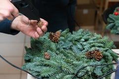De wevende workshop van de Kerstmiskroon Vrouwenhanden die die vakantiekroon verfraaien van nette takken, kegels en diverse organ royalty-vrije stock afbeeldingen