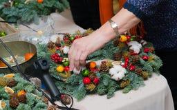 De wevende workshop van de Kerstmiskroon Vrouwenhanden die die vakantiekroon verfraaien van nette takken, kegels en diverse organ stock fotografie