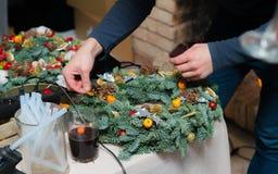 De wevende workshop van de Kerstmiskroon Vrouwenhanden die die vakantiekroon verfraaien van nette takken, kegels en diverse organ stock foto