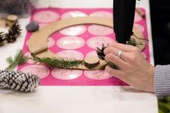De wevende workshop van de Kerstmiskroon Vrouwenhanden die die vakantiekroon verfraaien van nette takken, kegels en diverse organ royalty-vrije stock foto's