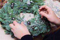 De wevende workshop van de Kerstmiskroon Vrouwenhanden die die vakantiekroon verfraaien van nette takken, kegels en diverse organ stock afbeeldingen