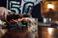 De whisky wordt gegoten in een glas van een fles stock foto
