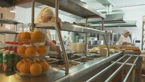 De Wideshotwerknemer van Kantine in Witte Algemeen maakt Voedsel op stock footage