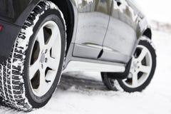 De wielen van de winterbanden op suvauto die in openlucht worden geïnstalleerd Stock Afbeelding