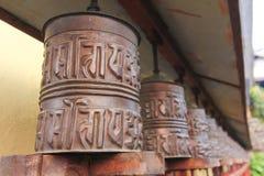 De wielen van het metaalgebed van Boeddhisme Tibetaans klooster van Nepal royalty-vrije stock afbeeldingen